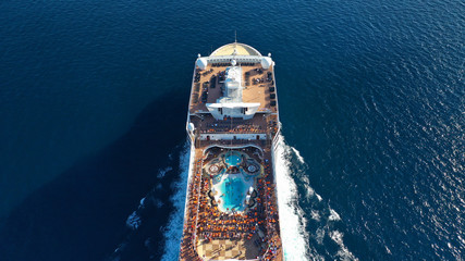 Aerial top view photo of huge cruise liner with pools and outdoor facilities cruising the Atlantic blue ocean