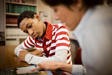Teenage boy reading in a classroom.