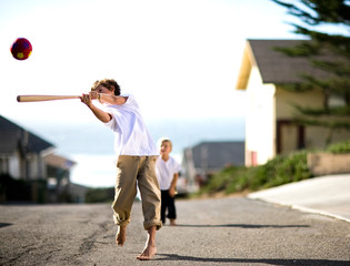 Two brothers playing baseball together on a street.