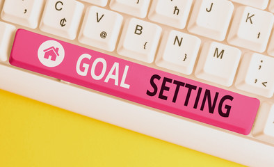 Writing note showing Goal Setting. Business concept for process of identifying something that you want to accomplish White pc keyboard with note paper above the white background