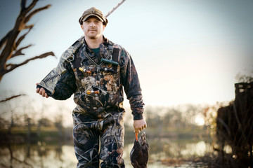 Portrait of a young adult man duck shooting with a gun by a lake.
