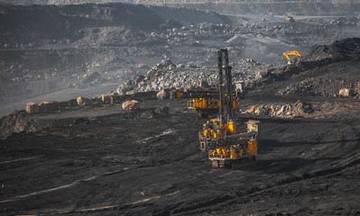 Open coal mine. Drilling machine borer installing cast explosives blasting