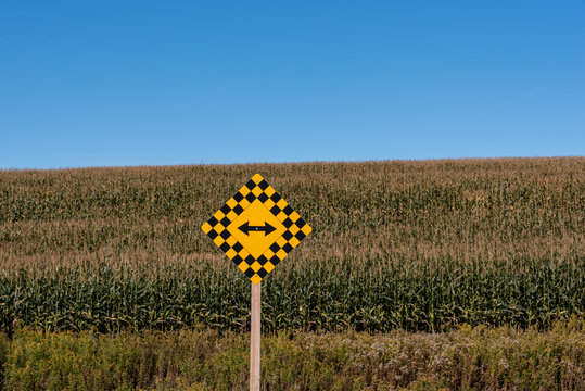 traffic signs in front of large corn field