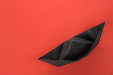 Black paper boat top view on red background