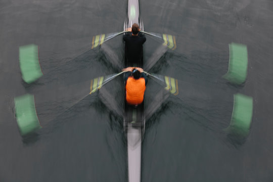Blurred motion overhead view of a double scull pairs boat, two oarsman in a sculling boat on the water, mid stroke.,Lake Union