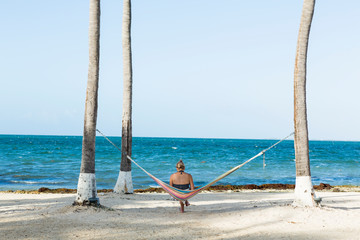 woman resting in hammock taking picture with smart phone, Grand Cayman Island