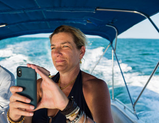 adult woman taking picture with smart phone, on boat