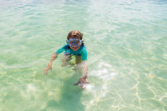 5 year old boy in the water holding a star fish, Grand Cayman Island