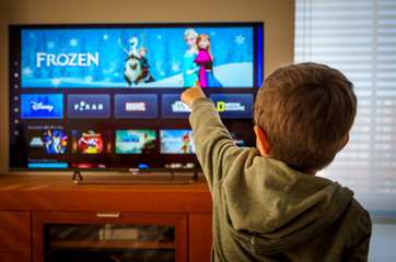 Barcelona, Spain. May 2019: Back view image of cute little boy watching the new Disney plus platform on TV