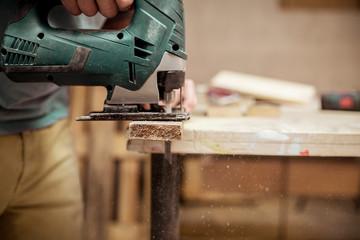 Close-up of carpenter cutting wood with jigsaw
