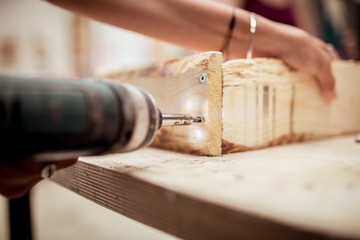 Cropped hands of female carpenter drilling wood at workbench in workshop
