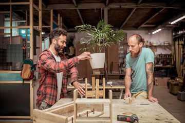 Male carpenter showing wooden plant pot holder to colleague while discussing at workbench in workshop