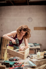 Female carpenter drilling wooden table while working at workshop