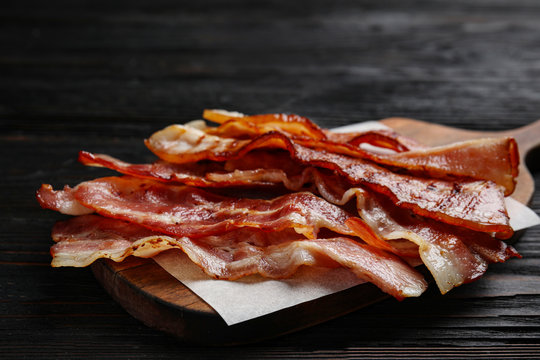 Slices of tasty fried bacon on black wooden table, closeup