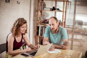 Smiling female carpenter using laptop while working with male colleague in office