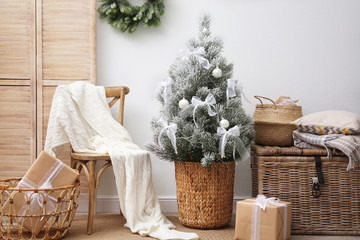 Stylish room interior with beautiful Christmas tree near white wall