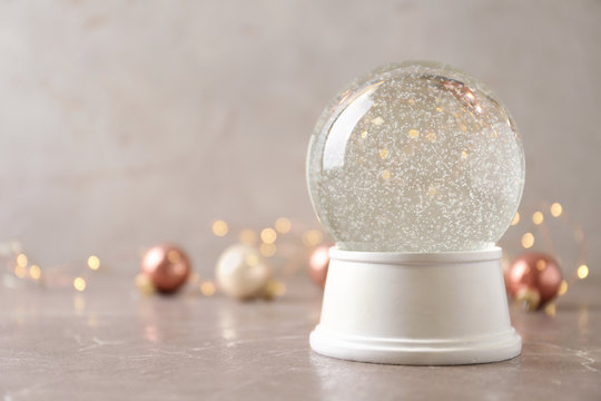 Snow globe and Christmas decorations on marble table against festive lights, space for text