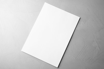 Blank paper sheet on light grey stone background, top view. Mock up for design