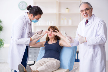 Two male doctors and young woman in plastic surgery concept