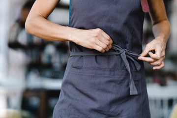 Woman tying her apron before work