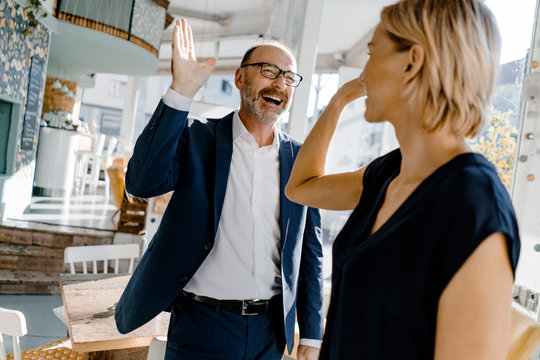 Business people high fiving in a coffee shop
