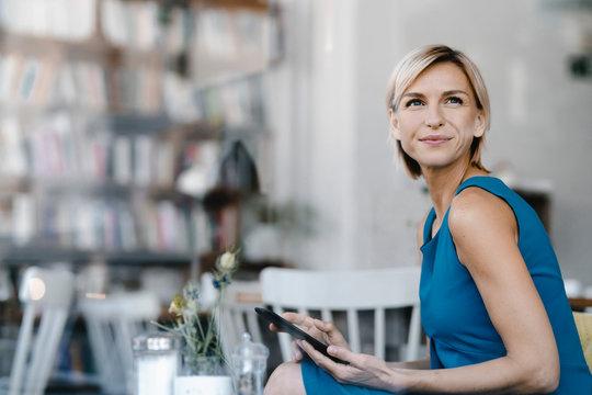 Businesswoman sitting in coffee shop, using digital tablet