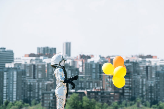 Boy dressed as an astronaut holding balloons in the city