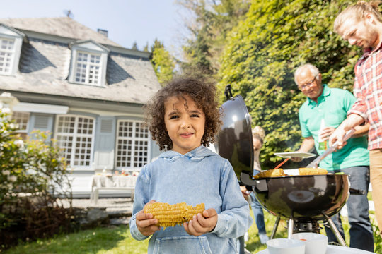 Portrait of boy with corn cob on a family barbecue in garden