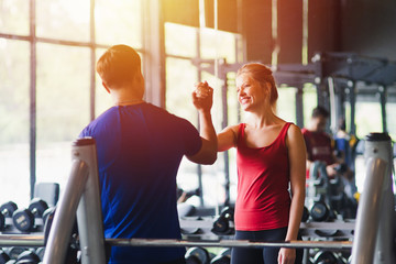 Poster Fitness Fitness woman and man with sportswear giving each other a high five while training on exercise at gym sport, bodybuilding, lifestyle and people concept