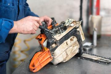 Mechanic repairing a chainsaw. Man repairing a chainsaw in workbench .