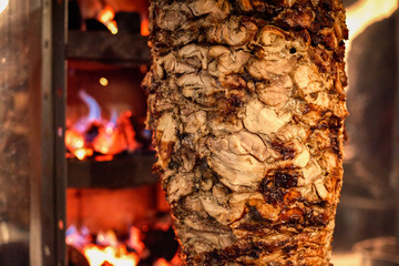 Close up shot of stacked meat roasting to be used in preparation of traditional Greek dish gyros or Turkish durum doner. shawarma
