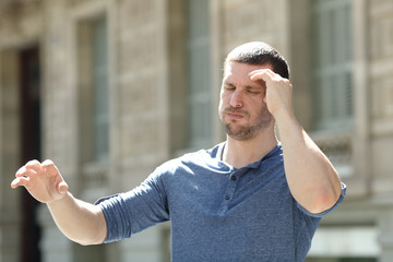 Dizzy adult man suffering headache in the street