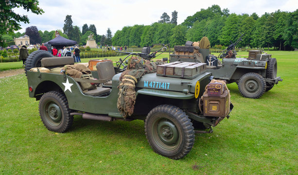 World War 2 Jeeps with  mounted Machine guns parked on grass.