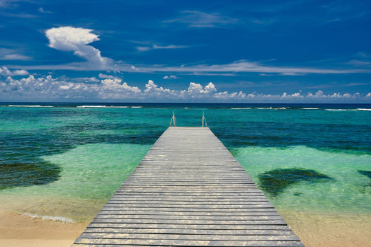 A beautiful wood dock leads out to the crystal clear and turquoise waters of the Cayman Islands in the tropical Britsh west indies