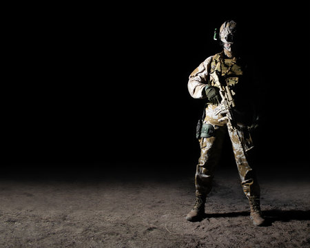 Fully equipped soldier standing with rifle on dark background.