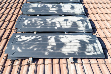 Black hot water solar system on an orange terracotta roof on a house.