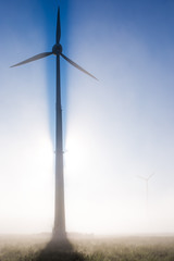 A wind turbine in the early morning in fog and backlight. Concept: modern energy production
