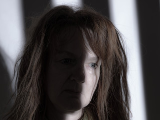 Portrait of a woman with health impairment. A grid casts a shadow on her face. Concept: health problems.