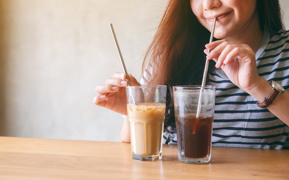 Closeup image of a beautiful asian woman drinking iced coffee with stainless steel straw