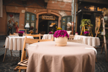 view of cafe table at city street with flowers