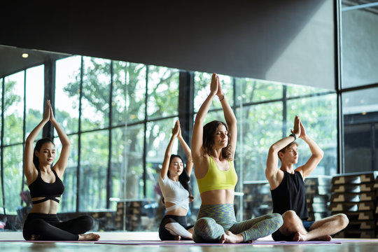 Group of young sporty attractive people practicing yoga lesson with basic pose with instructor, sitting together in exercise class, Warrior one pose, working out, indoor full length, studio background