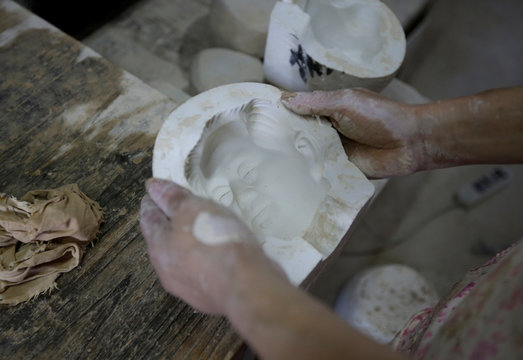 A ceramic artist holds a mold as she makes the head of a bust portraying late Chinese chairman Mao Zedong in Jingdezhen