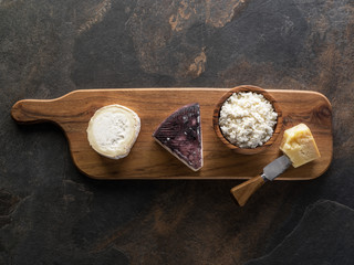 Wall Mural - Cheese platter with different homemade organic cheeses on stone background. Top view.