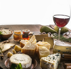 Wall Mural - Cheese platter with organic cheeses, fruits, nuts and wine. Tasty cheese starter.