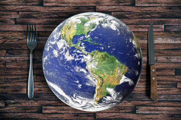 The planet Earth plate with a fork and knife on a wooden background. World hunger concept. Feed the world.