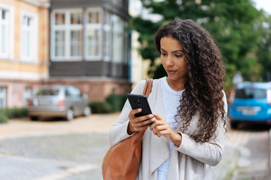 Young woman looking at her phone in consternation