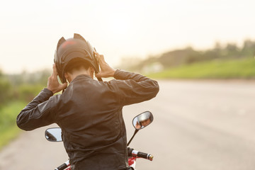 Handsome motorcyclist wear leather jacket and holding helmet on the road