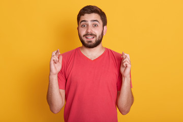 Lifestyle and people concept. Image og attractive guy waiting for special moment, young bearded man wearing red casual t shirt, keeping fingers while standing against yellow studio background.