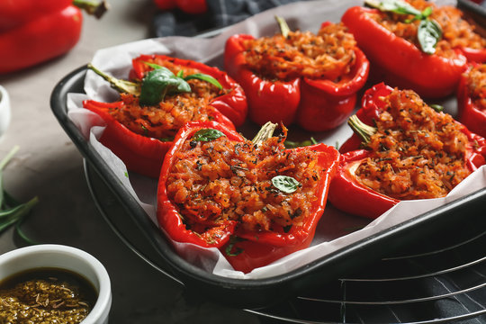 Baking dish with tasty stuffed pepper and sauce on table