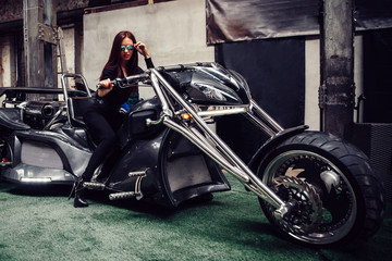 stylish young woman model posing near a chic tricycle.